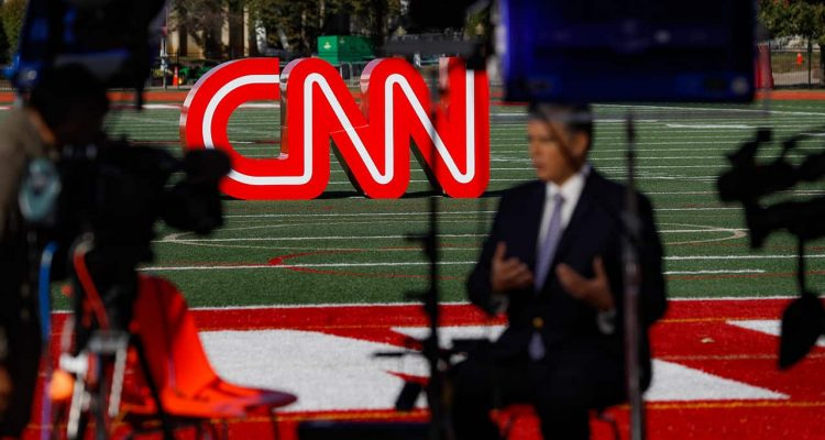 Photo of a journalist recording a video near a CNN sign