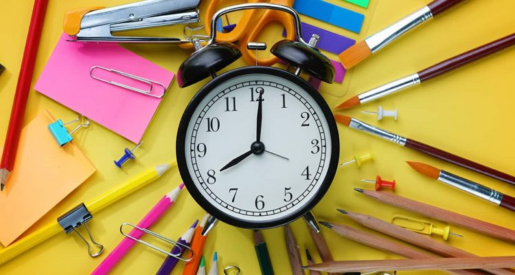 Photo of alarm clock against a backdrop of pens, rulers and paper signifying school start timesr