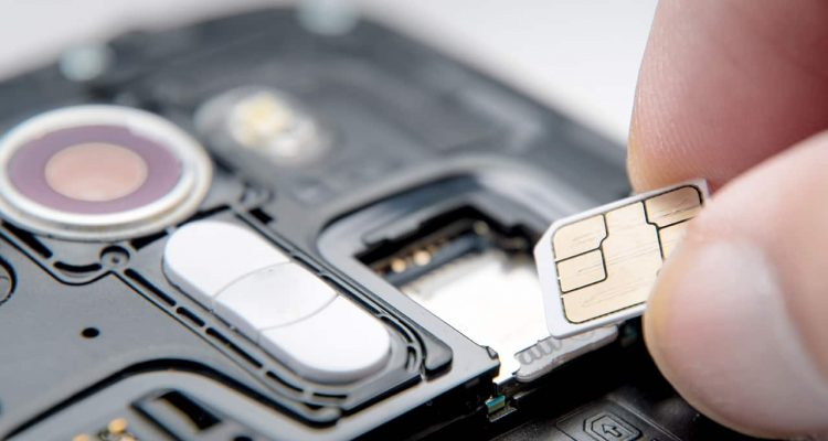 Photo of a SIM card and a cell phone