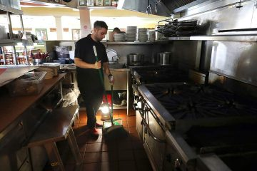 Photo of Salvador Espinosa sweeps in the kitchen of Mary's Pizza Shack