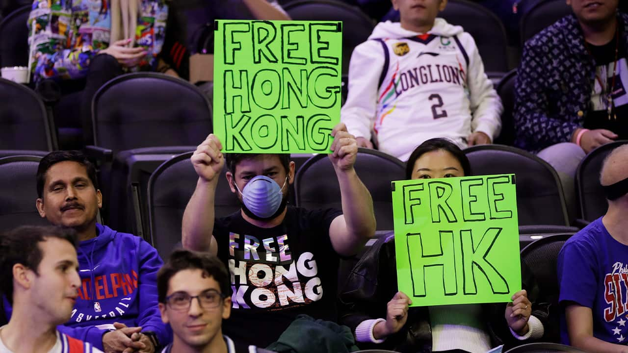 Photo of fans holding signs ahead of an NBA exhibition game