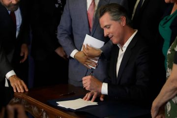 Photo of Gavin Newsom signing AB1482