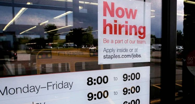 "Photo of ""Now Hiring"" sign on the front door of a Staples store"