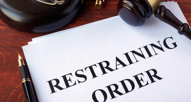 Photo of a restraining order on a desk with a gavel