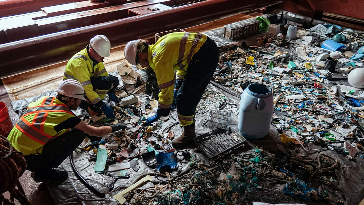 Photo of crew members sorting through plastic on board a support vessel