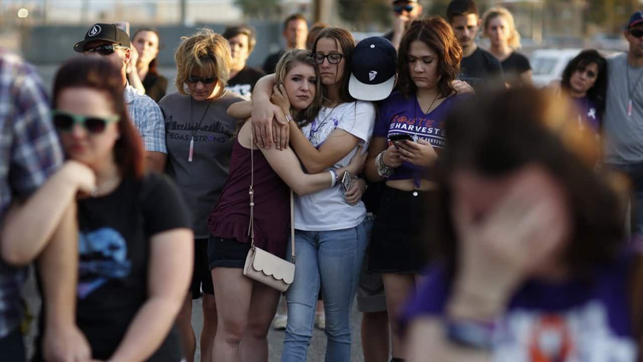 Photo of people comforting each other during a vigil in 2018