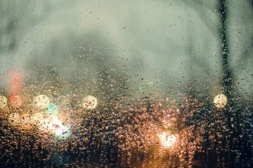 photo of rain and lights seen through a window