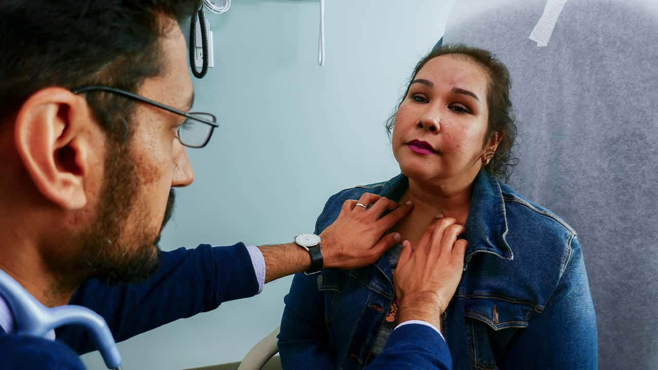 Photo of Dr. Moazzum Bajwa examining a patient's neck