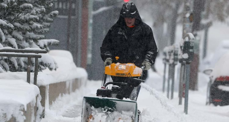 Photo of a man using a snowblower