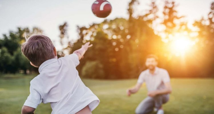 Photo of a son throwing a football to his dad