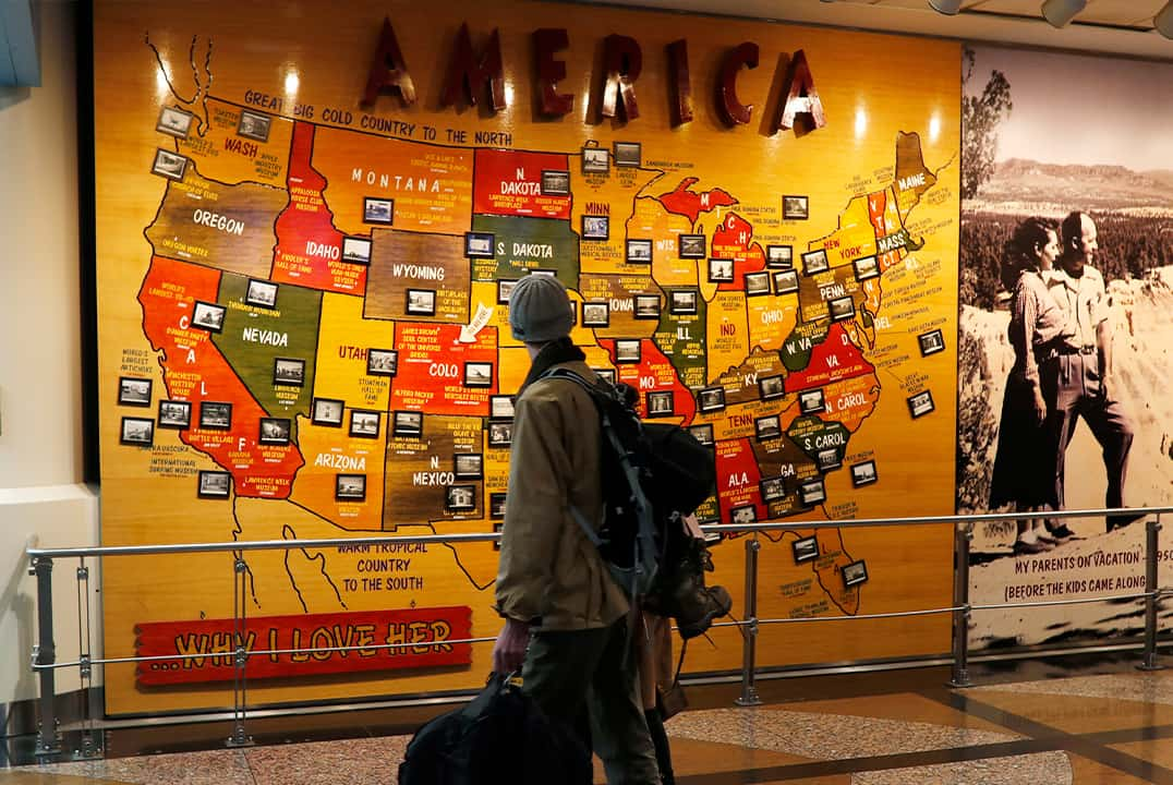 Photo of a traveler passing by a map of the U.S. at the Denver International Airport
