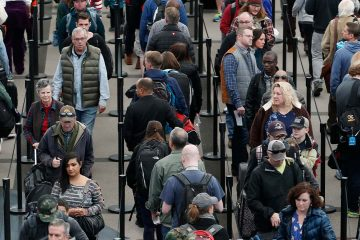Photo of travelers waiting in line at the Denver International Airport