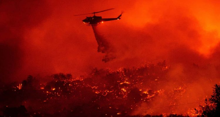 Photo of a helicopter dropping water on the Cave Fire