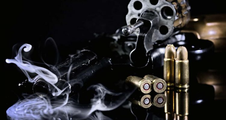 Photo of a Colt revolver, cartridges and smoke