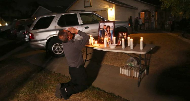Photo of Neej Xiong, uncle of shooting victim Kou Xiong, praying in front of a memorial during a candle light vigil in Fresno