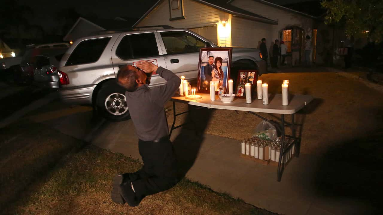 """In this photo taken Monday, Nov. 18, 2019, Neej Xiong, uncle of shooting victim Kou Xiong, prays in front of a memorial during a candlelight vigil in Fresno, Calif. A close-knit Hmong community was in shock after gunmen burst into a California backyard gathering and shot 10 men, killing four. """"We are right now just trying to figure out what to do, what are the next steps. How do we heal, how do we know what's going on,"""" said Bobby Bliatout, a community leader. (Larry Valenzuela/The Fresno Bee via AP)"""