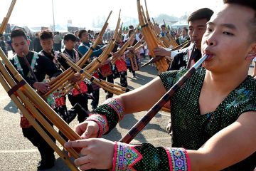 Photo of Phia Chia performing on a traditional Hmong instrument, the qeej