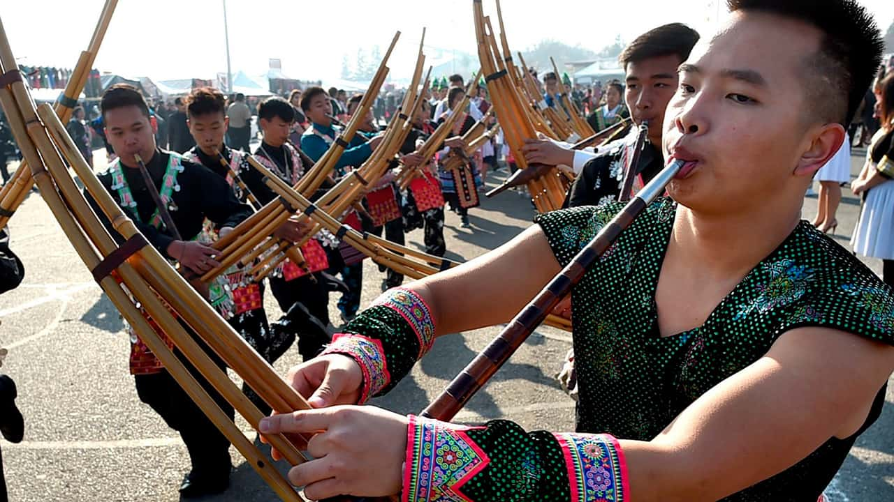 In this photo taken Dec. 26, 2017, Phia Cha, right, and other members of the Suab Hmoob Txuj Ci group perform on the traditional Hmong instrument, the qeej, during the grand opening parade during the Hmong Cultural New Year Celebration at the fairgrounds in Fresno, Calif. The country's small Hmong American population is reeling from the shooting deaths of four men at a backyard party at a Northern California central valley city. Fresno hosts a week-long New Year's party every year that draws tens of thousands of Hmong from around the country, complete with colorful traditional dress, song, and sports games. (John Walker/The Fresno Bee via AP)