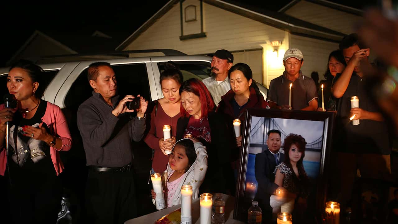 """In this photo taken Monday, Nov. 18, 2019, the wife and young daughter of shooting victim Kou Xiong stand among the crowd during the candle light vigil in his honor outside their home in Fresno, Calif. A close-knit Hmong community was in shock after gunmen burst into a California backyard gathering and shot 10 men, killing four. """"We are right now just trying to figure out what to do, what are the next steps. How do we heal, how do we know what's going on,"""" said Bobby Bliatout, a community leader. (Larry Valenzuela/The Fresno Bee via AP)"""