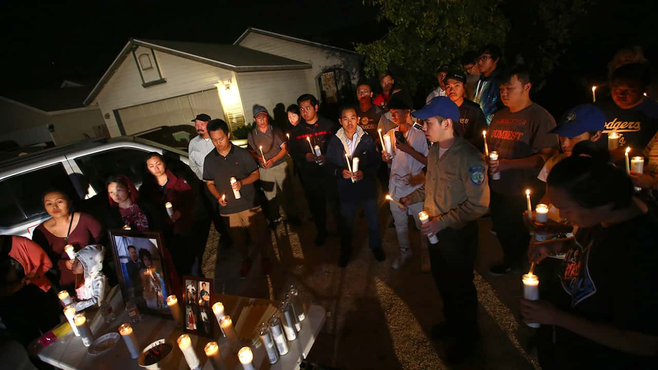 Photo of friends and family of shooting victim Kou Xiong during a candle light vigil in Fresno
