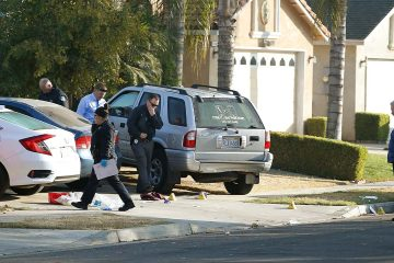 Photo of Fresno police investigators working in the driveway