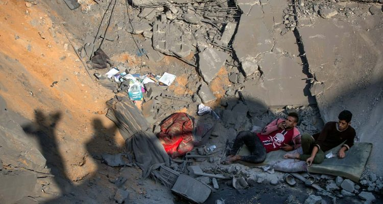 Photo of Palestinians sitting amid rubble