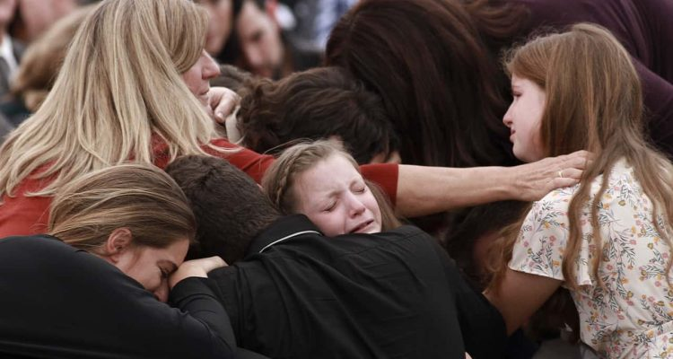 Photo of family and friends weeping at a funeral
