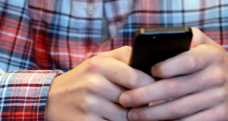 Photo of a person texting on their cellphone