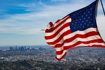 Photo of a flag waving with Los Angeles skyline in the background