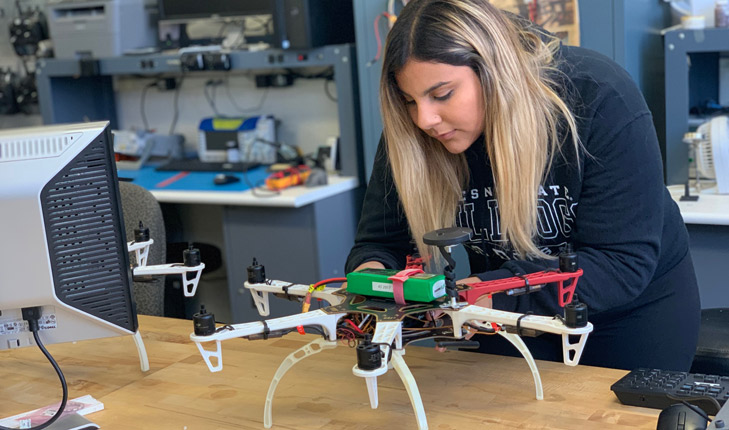 Photo of Samantha Saucedo working on a drone