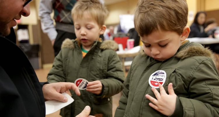 "Photo of kids putting on an ""I Voted"" sticker"