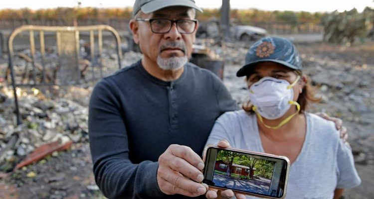 Photo of Justo and Bernadette Laos showing a photo of their home before it burned down