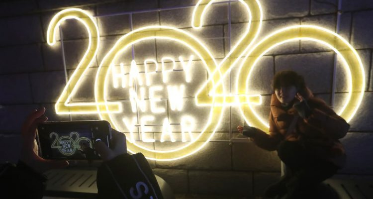 Photo of a woman posing next to a 2020 sign for a photo