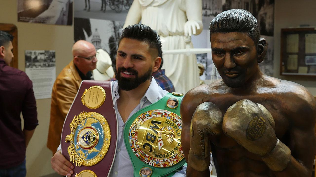 Photo of world boxing champion Jose Ramirez posing beside his statue in Fresno, California