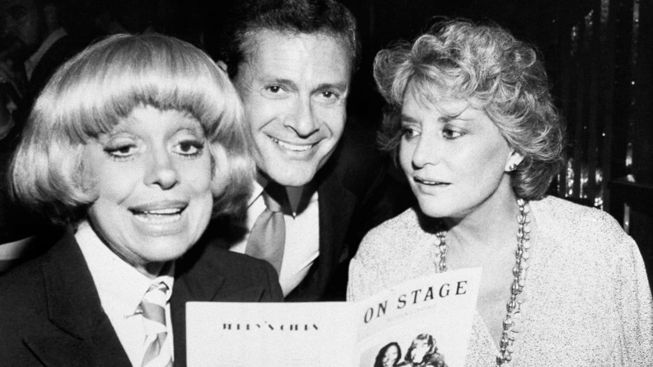 Photo of Carole Channing, left, and television personality Barbara Walters looking over the program with composer-lyricist Jerry Herman