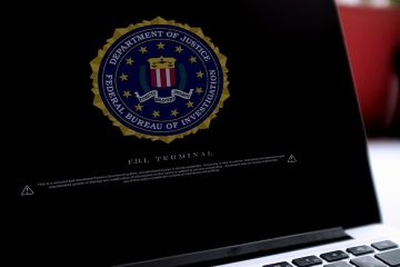 Photo of a laptop with a Department of Justice logo on the screens