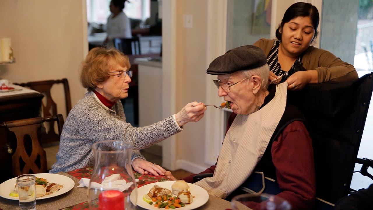 Photo of Betty Briggs feeding her husband, Bob