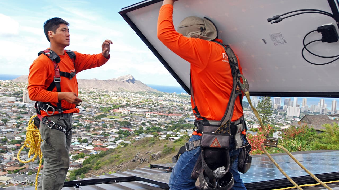 Photo of solar panel installers on a roof in Honolulu
