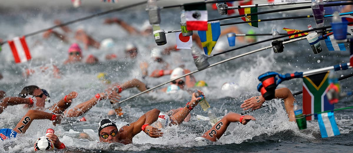 Photo of swimmers reaching for drinking bottles during the men's 10k open water swim