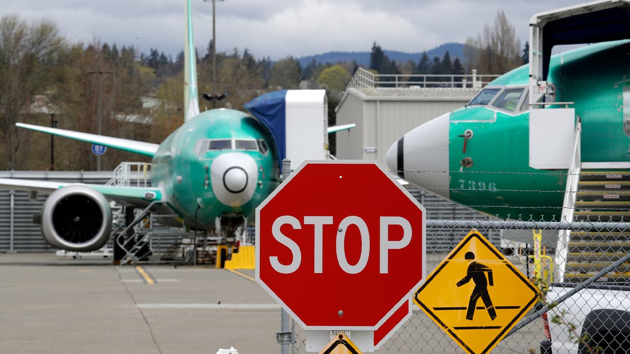 Photo of Boeing 737 MAX 8 jets are parked behind a stop sign