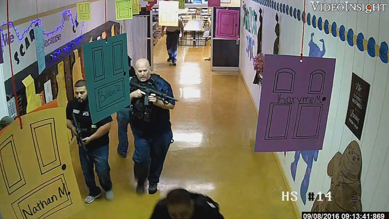 Photo of armed law enforcement officers move through a hallway at Alpine High School in Alpine, Texas