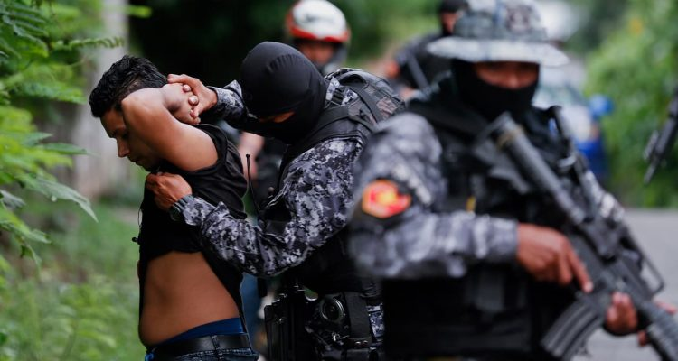 Photo of police frisking a man in El Salvador