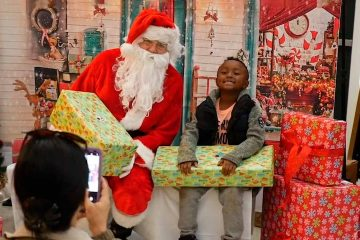 Photo of a young student sitting next to Santa Claus with a wrapped gift