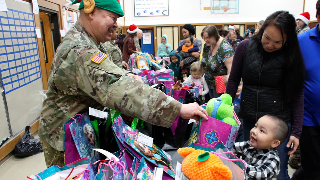 Photo of Alaska National Guard Staff Sgt. Joseph Sallaffie handing a gift bag to Corban Jimmy while Marlene Black looks on