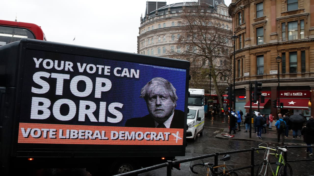 Photo of a vehicle brandishing an election campaign poster for the Liberal Democrats party