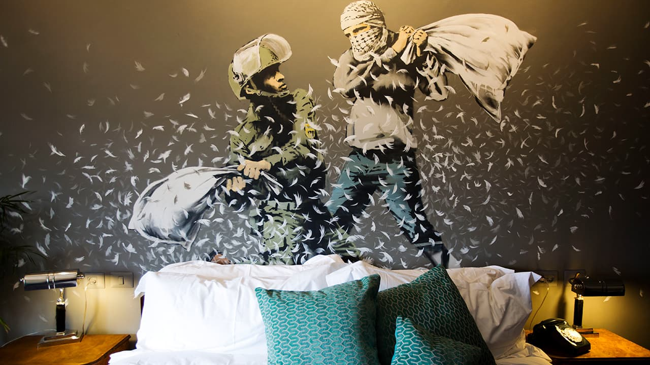 Photo of a Banksy wall painting showing an Israeli border police officer and a Palestinian in a pillow fight