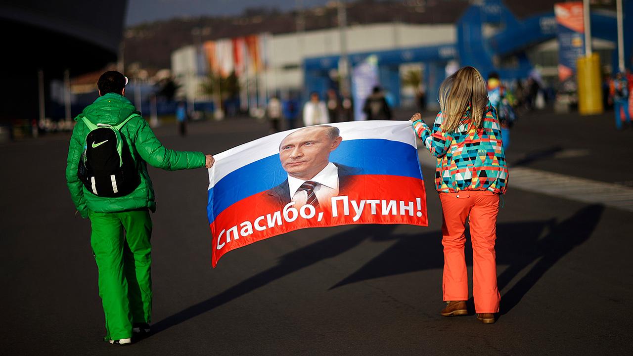 Photo of Veleriya Obarevich, right, and Yan Shamilov carrying a Russian flag