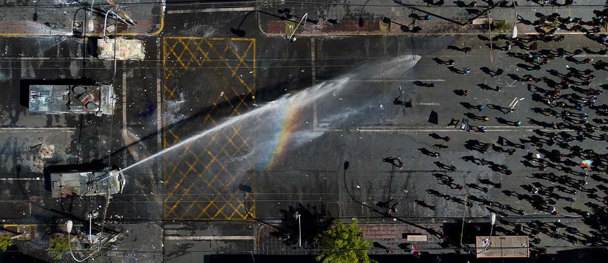 Photo of a police water canon spraying protestors in Chile