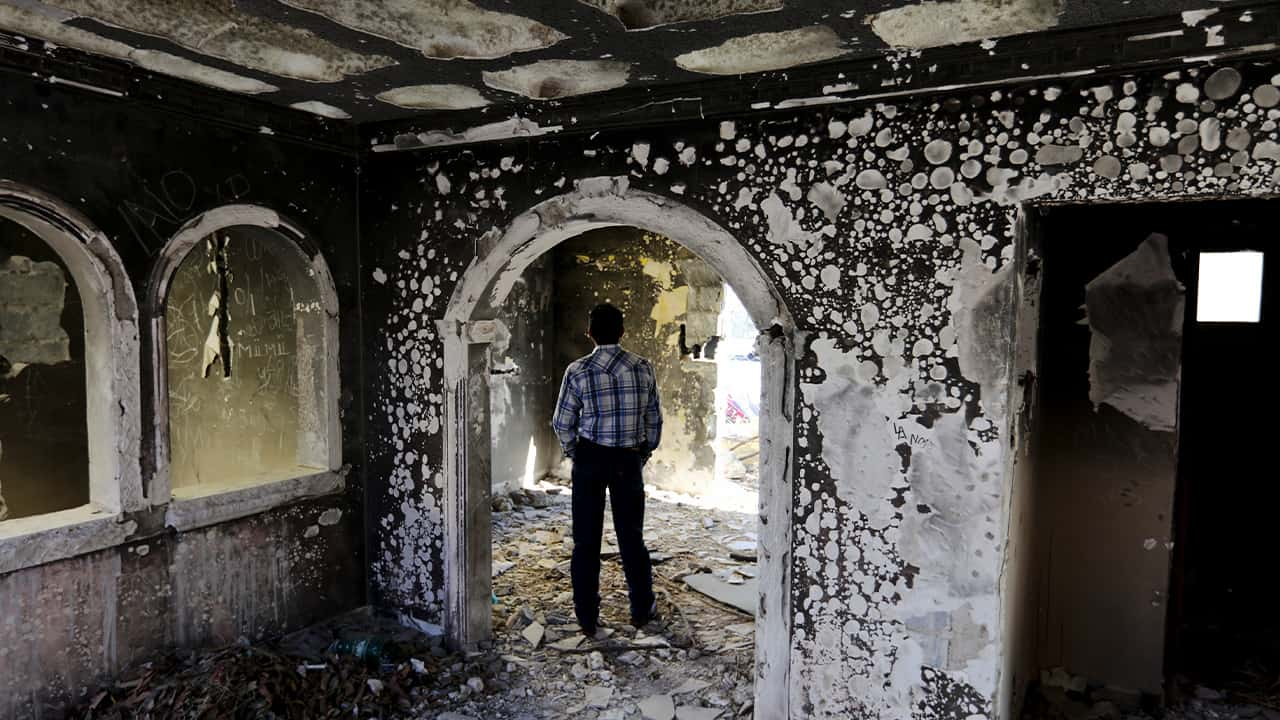 Photo of a former policeman walking through an abandoned home torched by the Zetas cartel