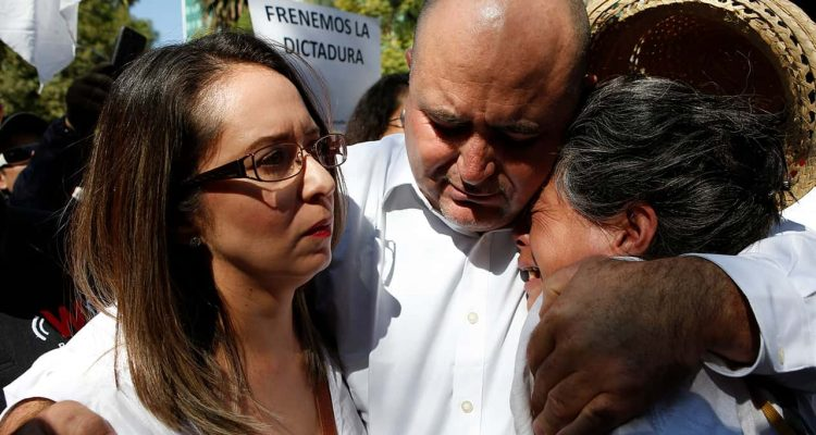 Photo of Julian LeBaron embracing two women before a protest
